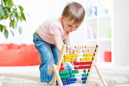 nursery: Muchacha del niño que juega con el juguete contador en la guardería