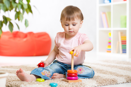 assiduous: Cute toddler girl playing in nursery room