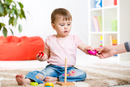 one room school house: Child girl playing with toy indoors at home