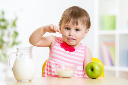 baby with spoon: Child girl eating food itself with spoon