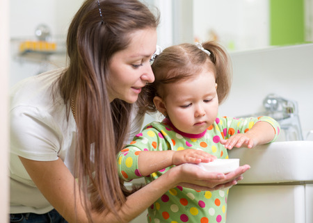 de higiene: Niño de la muchacha y lavado madre manos con jabón en el baño. Concepto de higiene.