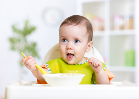 Happy cute baby kid eating food itself with spoon