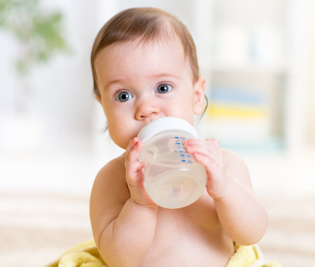 cute baby holding bottle and drinking water