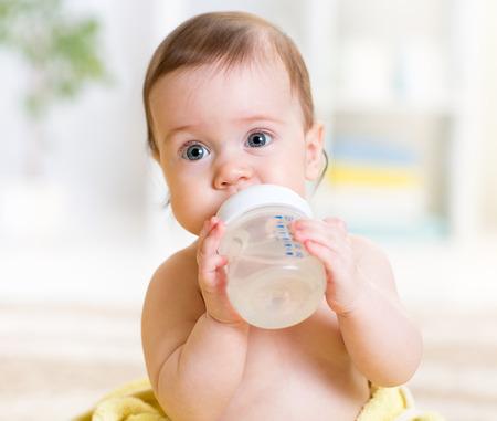 teteros: lindo bebé sosteniendo la botella y el agua potable