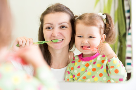 mother teaching kid teeth brushing in bathroom