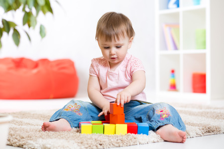 baby blocks: kid girl playing wooden block toys at home
