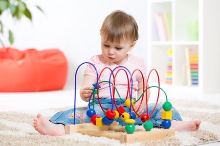 indoors: kid girl plays with educational toy indoors Stock Photo