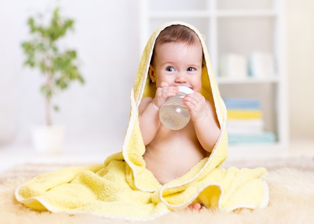 baby girl drinks water from bottle wrapped towel at home
