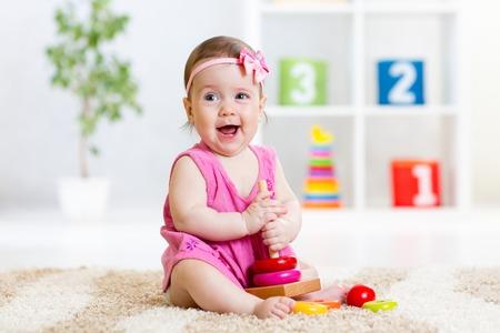 piramide humana: lindo bebé jugando con pirámide de juguete colorido en casa Foto de archivo