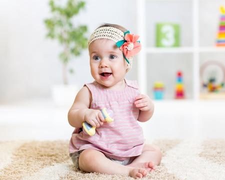 linda niña jugando con el juguete en el interior Foto de archivo