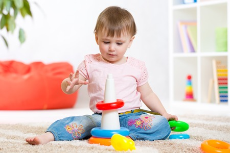 assiduous: Toddler child playing with wooden blocks at home