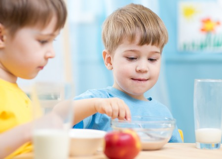 eating dinner: children eating healthy food at home or kindergarten