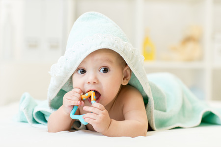 girl with towel: baby with teether in mouth under bathing towel at nursery