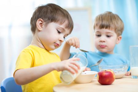 cereal: niños comiendo alimentos saludables en jardín de infantes o guardería Foto de archivo