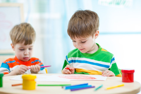 day care center: smiling children draw and paint at home or day care center Stock Photo