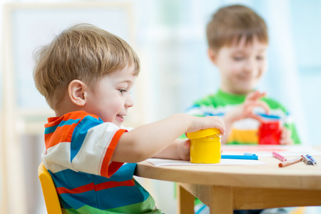 kindergarten education: children play and paint at home or kindergarten or playschool or daycare