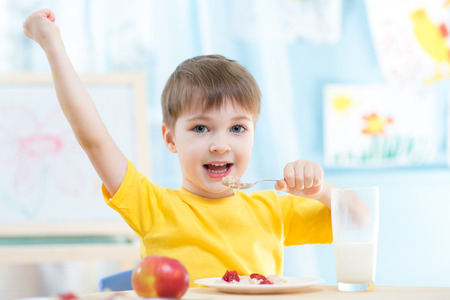 morning breakfast: Adorable child boy eating cereal with strawberries and drinking milk Stock Photo