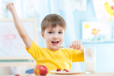comiendo cereal: Niño chico adorable que come cereal con fresas y leche de consumo