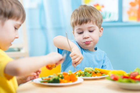 dinner: kids children eating vegetables in kindergarten or at home