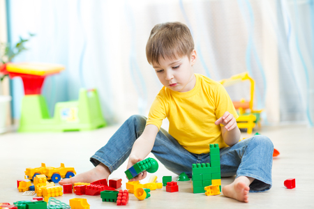 toy: kid boy plays with constructor toys