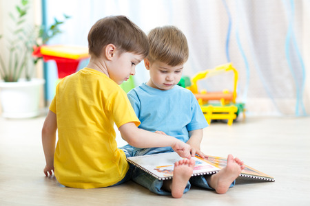 children read a book sitting on floor Stock Photo