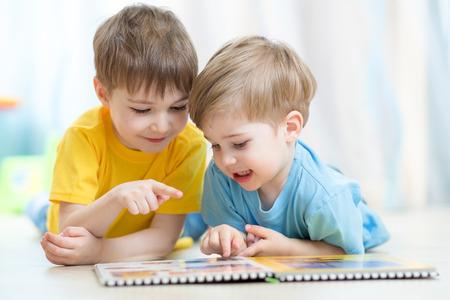 familias jovenes: Niños hermanos practican leyendo juntos mirando el libro que pone en el suelo