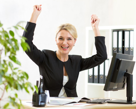 successful woman: Successful middle-aged business woman with arms up sitting at pc in office