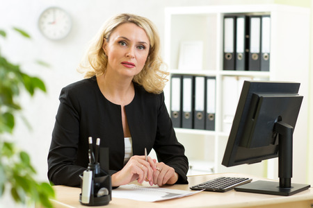Smiling middle-aged business lady working in office
