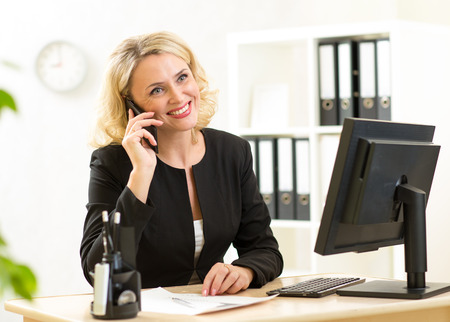 carefree: cute middle aged office worker talking on cell phone in office Stock Photo