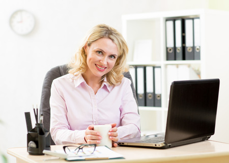mujer trabajadora: Middle aged businesswoman working on laptop and drinking coffee Foto de archivo