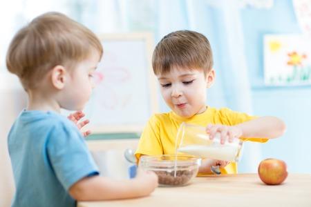 niños comiendo: pequeños niños que comen alimentos saludables en el hogar