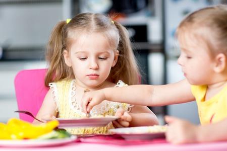 niños comiendo: los niños comer espaguetis con verduras en la guardería o en casa Foto de archivo