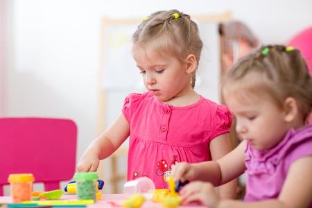 Las niñas aprenden a trabajar plastilina de colores en el cuarto de niños en el hogar o centro de cuidado de día Foto de archivo