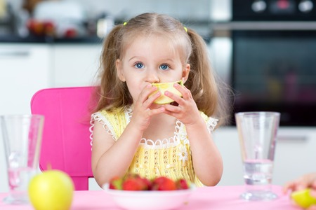 manzana agua: muchacha del cabrito comer comida saludable en el hogar