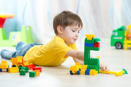 kid boy playing toy blocks on floor at home