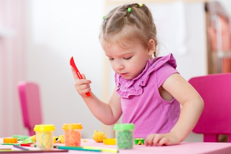tinkering: kid girl drawing and making by hands at nursery or kindergarten
