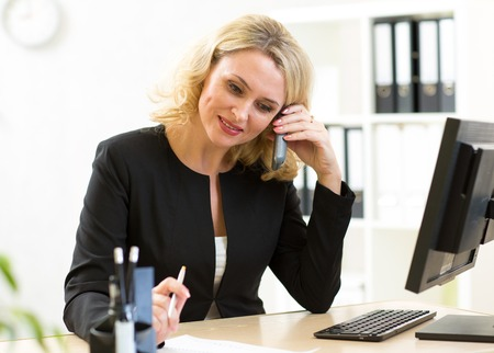office attire: Business woman talks on phone working in office