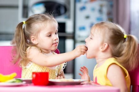 sharing: Two little children toddlers eating meal together, one girl feeding sister in sunny kitchen at home
