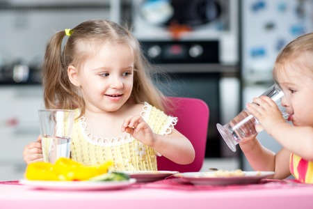girl drinking: Cute little children drinking water at daycare or nursery