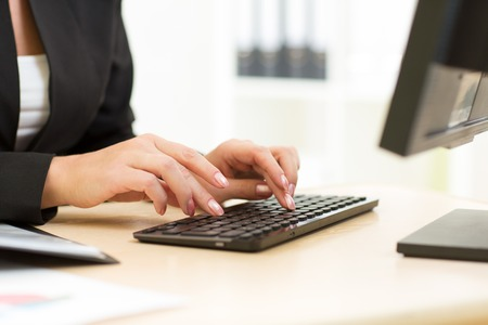 office attire: Office worker typing on keyboard in office Stock Photo