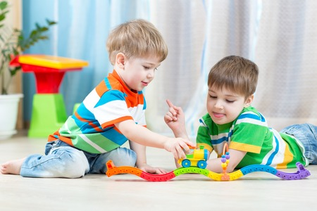 babies playing: boys children playing rail road toy in nursery