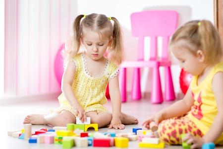 Enfants jouant jouets de bloc en salle de jeux à la pépinière