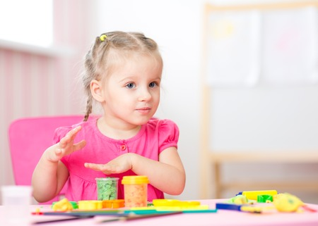 playschool: kid girl playing with play clay at home or  playschool Stock Photo