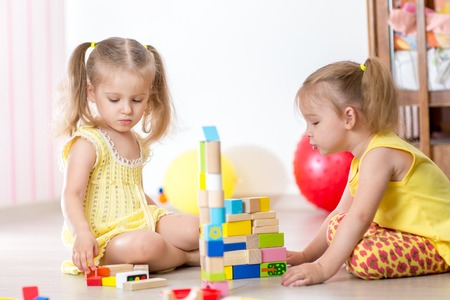 play blocks: Cute kids playing with constructor toys at home Stock Photo
