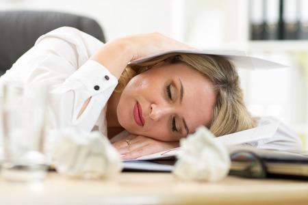 agotado: Empresaria femenina agotado haciendo papeleo mientras está sentado en su escritorio Foto de archivo