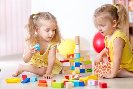 ni�os jugando: ni�os que juegan los juguetes de madera en la casa o el jard�n de infantes Foto de archivo