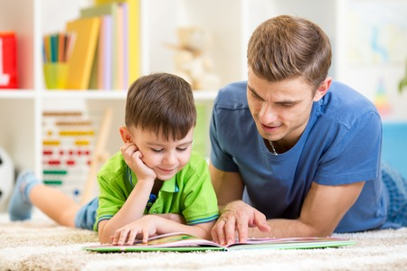 cute little boy and his dad read book together Stock Photo