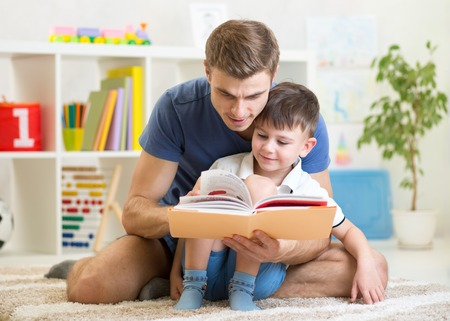 kid boy and father reading a book indoors