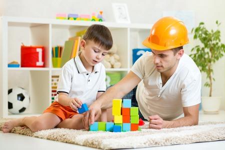 kind jongen en vader spelen bouwers in de kwekerij thuis