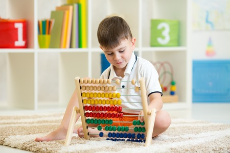 math: preschooler child boy playing with counter toy Stock Photo